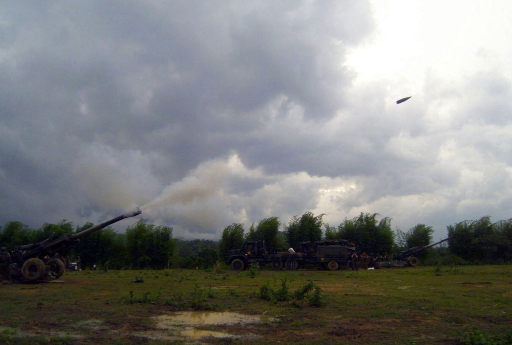 US Marine Corps (USMC) Marines assigned to S/Battery, 5th Battalion, 10th Marines, fire the M198 155mm Howitzer, and launch a projectile towards its target, during a live fire exercise at Gun Position 10, Pong Nam Ran, Thailand, during Exercise COBRA GOLD 2003