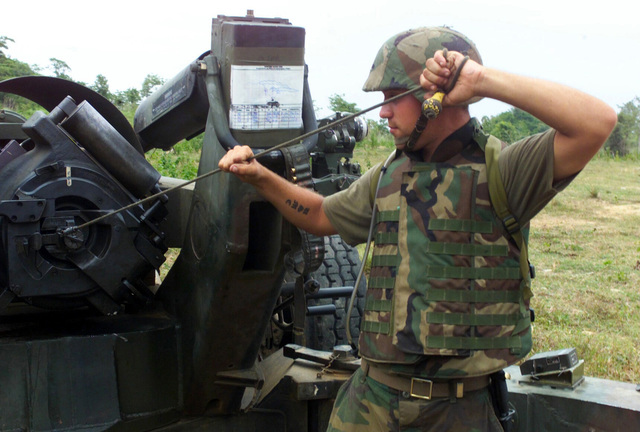 US Marine Corps (USMC) Private First Class (PFC) Peter Tierno, S/Battery, 5th Battalion, 10th Marines, simulates pulling the lanyard on a M198 155mm Howitzer, during a live fire exercise at Gun Position 10, Pong Nam Ran, Thailand, during Exercise COBRA GOLD 2003