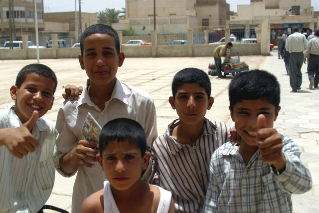 A group of Iraqi youths show their support at the Al Moter Secondary School, located in the town of Al Hillah, Iraq, where local Officials and US Army (USA) Soldiers and US Marine Corps (USMC) Marines assigned to Civil Affairs are paying the salary wages for Teachers as well as giving 20 dollars gifts to help support school activities and boost morale, while deployed in Iraq, supporting Operation IRAQI FREEDOM