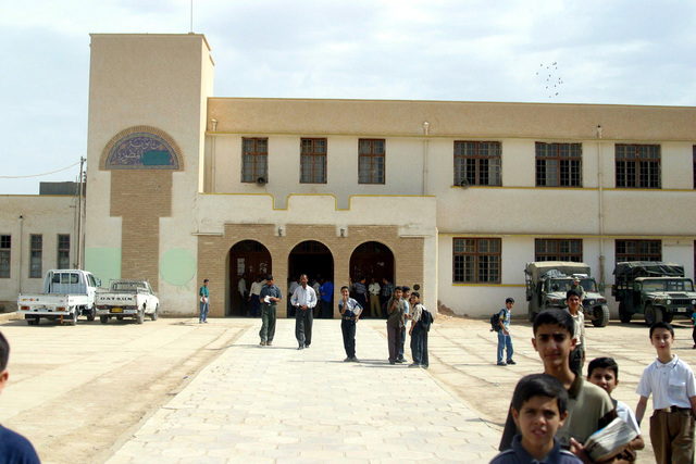 Iraqi students and teachers walk the campus at the Al Moter Secondary School, located in the town of Al Hillah, Iraq. Inside US Army (USA) Soldiers and US Marine Corps (USMC) Marines assigned to Civil Affairs pay salary wages for Iraqi Teachers as well as give 20 dollars gifts to help support school activities and boost morale, while deployed in Iraq, supporting Operation IRAQI FREEDOM