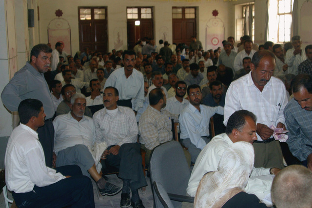 Iraqi teachers assemble inside the auditorium at the Al Moter Secondary School, located in the town of Al Hillah, Iraq where local Officials and US Army (USA) Soldiers and US Marine Corps (USMC) Marines assigned to Civil Affairs are paying the salary wages for Teachers as well as giving 20 dollars gifts to help support school activities and boost morale, while deployed in Iraq, supporting Operation IRAQI FREEDOM
