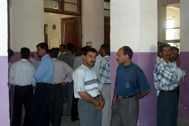 Iraqi Teachers line up inside the auditorium at the Al Moter Secondary School, located in the town of Al Hillah, Iraq. Inside US Army (USA) Soldiers and US Marine Corps (USMC) Marines assigned to Civil Affairs pay salary wages for Iraqi Teachers as well as give 20 dollars gifts to help support school activities and boost morale, while deployed in Iraq, supporting Operation IRAQI FREEDOM