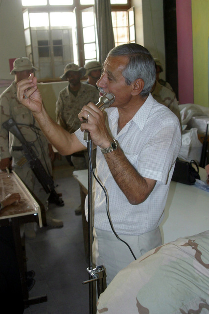 Mr. Hamed Abraham, a Sports Teacher at the Al Moter Secondary School, located in the town of Al Hillah, Iraq, speaks to local teachers about maintaining organization as US Army (USA) Soldiers and US Marine Corps (USMC) Marines assigned to Civil Affairs are pay the salary wages for Iraqi Teachers as well as give 20 dollars gifts to help support school activities and boost morale, while deployed in Iraq, supporting Operation IRAQI FREEDOM