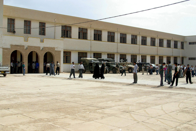 US Army (USA) Soldiers and US Marine Corps (USMC) Marines assigned to Civil Affairs arrive at the Al Moter Secondary School, located in the town of Al Hillah, Iraq. Marines and Soldiers of Civil Affairs pay salary wages for Iraqi Teachers as well as give 20 dollars gifts to help support school activities and boost morale, while deployed in Iraq, supporting Operation IRAQI FREEDOM