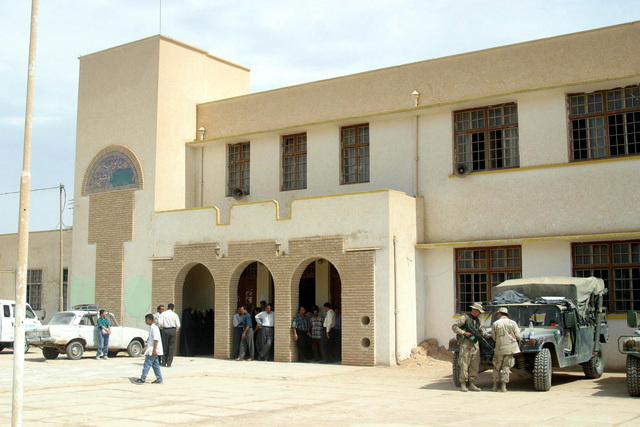 US Army (USA) Soldiers and US Marine Corps (USMC) Marines assigned to Civil Affairs arrive at the Al Moter Secondary School, located in the town of Al Hillah, Iraq. Marines and Soldiers of Civil Affairs are here to pay the salary wages for Iraqi Teachers as well as give 20 dollars gifts to help support school activities and boost morale, while deployed in Iraq, supporting Operation IRAQI FREEDOM