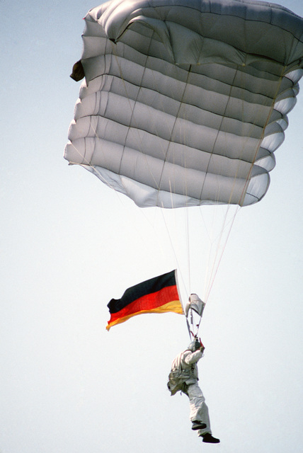 A member of the 317th Combat Control Team parachutes flying the national flag of the Federal Republic of Germany during the VOLANT RODEO '84 tactical airdrop competition
