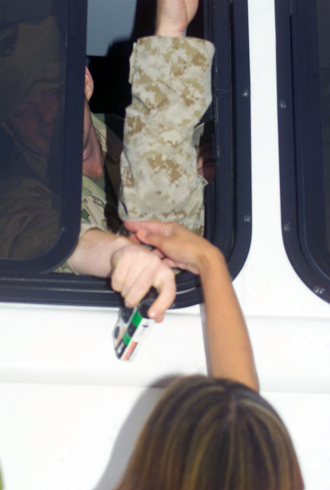 Myreen Panganiban gets a quick touch of her fianc, Corporal (CPL) Jason Martinez, on the bus arriving from March AFB. CPL Martinez, Headquarters Battalion (HQ BN), 1ST Marine Division (1MARDIV), Camp Pendleton, California, is returning from a six-month deployment in support of Operation IRAQI FREEDOM. Operation IRAQI FREEDOM is the multinational coalition effort to liberate the Iraqi people, eliminate Iraq's weapons of mass destruction and end the regime of Saddam Hussein
