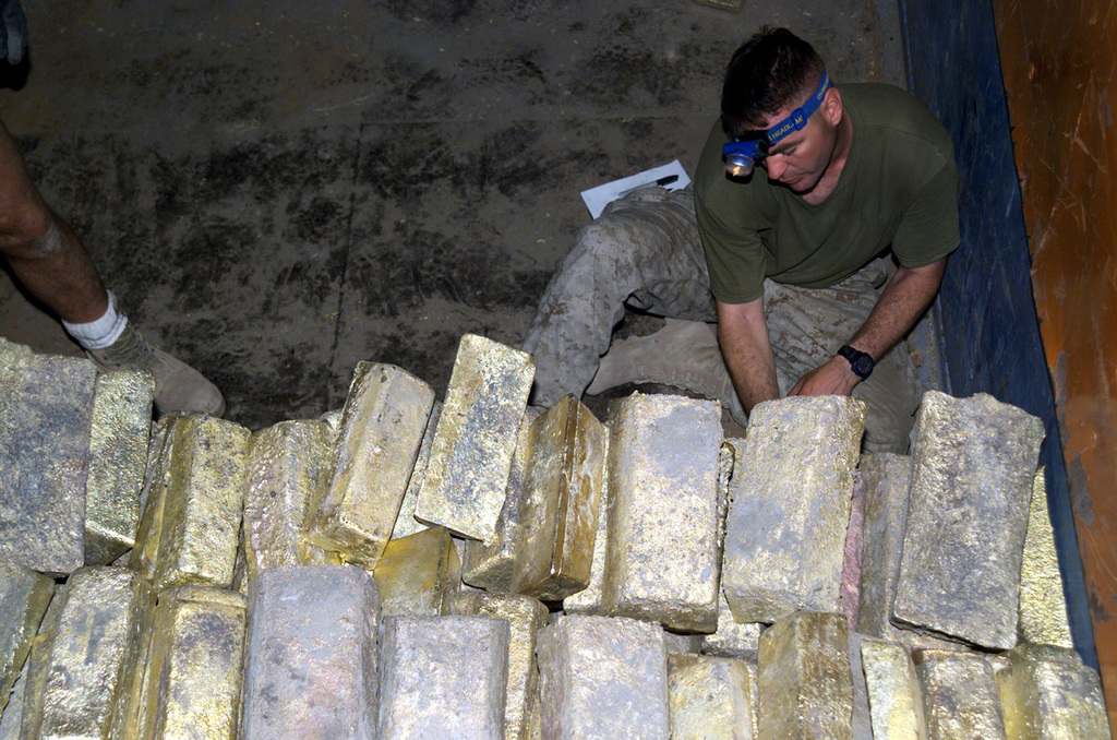 US Marine Corps (USMC) STAFF Sergeant (SSGT) Richard Beauchamp, 2nd Battalion, 25th Marines (2/25), Weapons Company, Garden City, New York (NY), counts the stacked brass ingots found at a check point during a patrol during Operation IRAQI FREEDOM