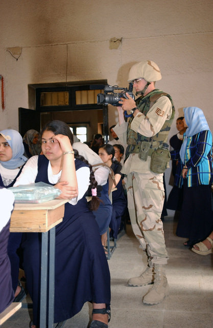 US Air Force (USAF) Videographer, STAFF Sergeant (SSGT) Kevin Davidson uses a digital video camera to document activities during a diplomatic visit to an all Girls school, in the City of Kirkuk, Iraq, during Operation IRAQI FREEDOM. During the visit an Iraqi government advisor spoke with students about the future of the new Iraq