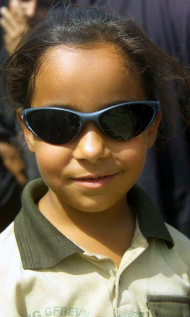 Portrait of Zehneb, an Iraqi girl, wearing the photographers sunglasses to pose for the camera while waiting in a propane distribution site in the Iraqi City of Al-Kut, during Operation IRAQI FREEDOM