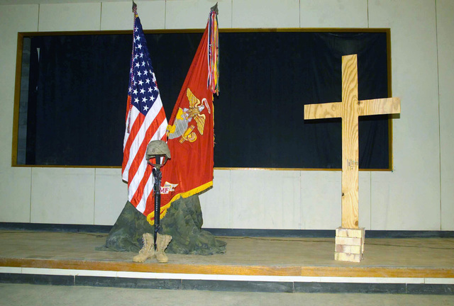 A Fallen Marine Memorial and a wooden Cross honoring US Marine Corps (USMC) Private First Class (PFC) Ryan R. Cox, 1ST Battalion, 7th Marine Regiment, 1ST Marine Division. PFC Cox died as a result of wounds received from a non-combat weapon discharge near An Najaf, Iraq, during Operation IRAQI FREEDOM