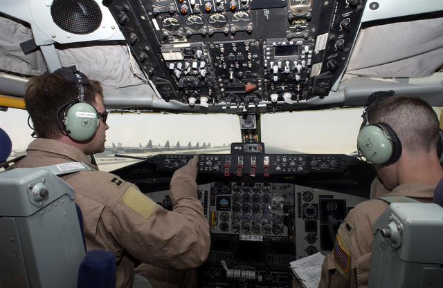 US Air Force (USAF) Captain (CAPT) Chris Randall, 304th Expeditionary Air Refueling Squadron (EARS), a KC-135 Stratotanker pilot, talks with First Lieutenant (1LT) Allister Dopp, about wind direction prior to take off during Operation IRAQI FREEDOM