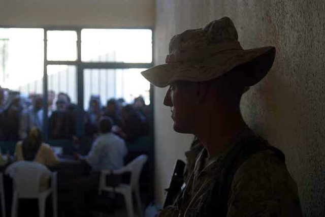US Marine Corps (USMC) Private First Class (PFC) Josh Secord, assigned to Alpha/Company, 1ST Battalion, 4th Marines, provides security as local Iraqi citizens arrive at a distribution center in Ah Hillah, Iraq. Elderly and handicapped citizens receive a pension of 15 dollars, as a gift from US Navy (USN) Sailors and US Marine Corps (USMC) Marines assigned to 1ST Battalion, 4th Marines, deployed to Iraq, in support of Operation IRAQI FREEDOM
