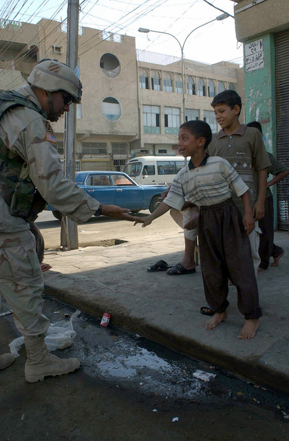 US Army (USA) Sergeant First Class (SFC) Morales, Scout Platoon, 1-64 Armor Battalion, 2nd Brigade, 3rd Infantry Division (Mechanized), slaps hands with an Iraqi boy while on patrol in Falluja, Iraq, during Operation IRAQI FREEDOM