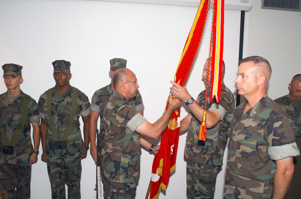 US Marine Corps (USMC) Sergeant Major (SGM) Oliva, Headquarters Battalion, Marine Forces Reserves (MFR), receives the Unit Colors from US Marine Corps (USMC) Lieutenant Colonel (LTC) Lloyd, Out-going Commander, Headquarters Battalion, MFR, as USMC LTC Gardner (foreground), In-Coming Commander, Headquarters Battalion, MFR, stands by to receive the Colors, during the Change of Command Ceremony held at MFR Headquarters Battalion, New Orleans, Louisiana (LA)