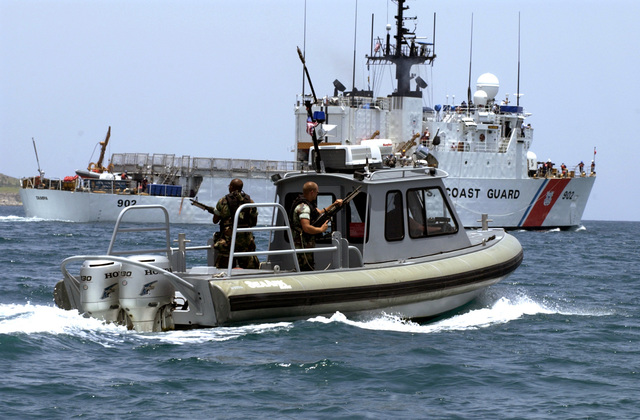 US Marine Corps (USMC) Marines and US Navy (USN) Sailors assigned to Security Harbor Defense at Guantanamo Bay Navy Base, use a SEAARK Deployable Pursuit Boat (DPB), armed with two 7.62mm M60 general-purpose machine guns, to escort the US Coast Guard (USCG) FAMOUS CUTTER CLASS; USS TAMPA (WMEC 902) through the waters of the southern boundary of Guantanamo Bay. Naval Station Guantanamo Bay Security Harbor Defense provides marine security throughout the Guantanamo Bay facility