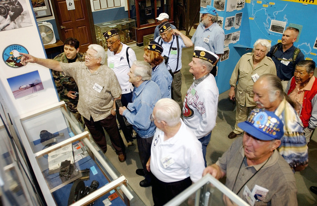 """William """"Bill"""" Rogister, former 6th Combat Camera Unit Photographer, talks to a group of International Combat Camera Association (CCA) and Veterans of Foreign Wars (VFW) members about combat camera pictures displayed at the March Field Museum during an Open House"""