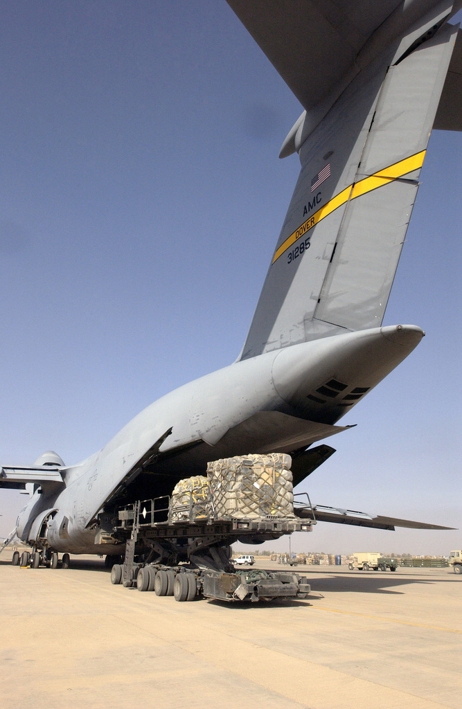 A US Air Force (USAF) C-5 Galaxy cargo aircraft from the 312th Airlift Squadron (AS), Dover Air Force Base (AFB), Delaware, and its personnel unloads cargo on the ramp at Baghdad International Airport (BIAP), during a redeployment mission in support of Operation IRAQI FREEDOM