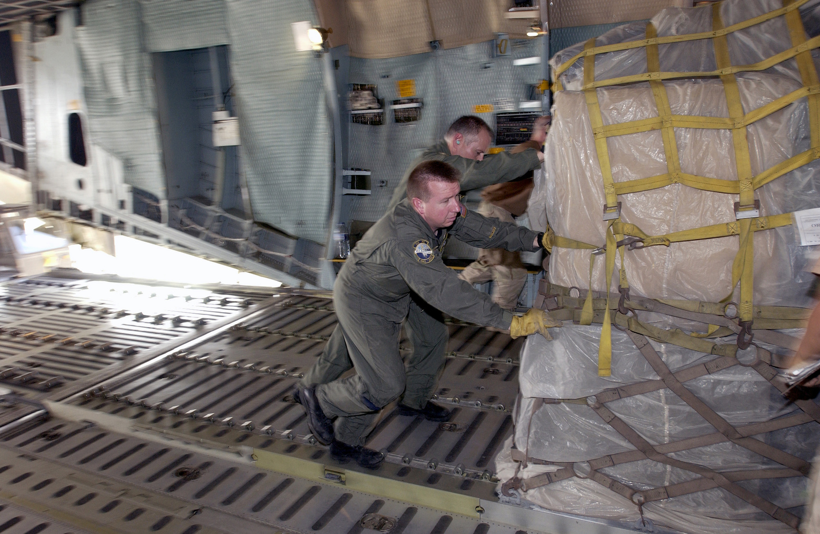 US Air Force (USAF) Technical Sergeant (TSGT) Eric J. Priest, a Loadmaster assigned to the 312th Airlift Squadron (AS), Dover Air Force Base (AFB), Delaware, pushes a pallet of redeployment equipment off of a C-5 Galaxy cargo aircraft during a redeployment mission in support of Operation IRAQI FREEDOM