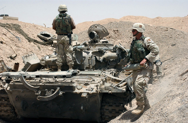 US Army (USA) Soldiers assigned to A/Company, 10th Engineers Battalion, 2nd Brigade, 3rd Infantry Division (Mechanized) remove live ammunition from a destroyed Iraqi T-55 Main Battle Tank (MBT) located outside of Fallujah, Iraq, during Operation IRAQI FREEDOM
