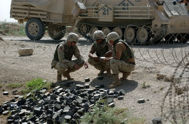 US Army (USA) STAFF Sergeant Joe Robsky, 759th Explosive Ordnance Disposal (EOD), shows two USA Soldiers assigned to A/Company, 10th Engineers Battalion, 2nd Brigade, 3rd Infantry Division (Mechanized), where the fuse is located on an Iraqi PMN Anti-Personnel (AP) mine, while working to clear an area where a large number of them were found outside of Fallujah, Iraq, during Operation IRAQI FREEDOM