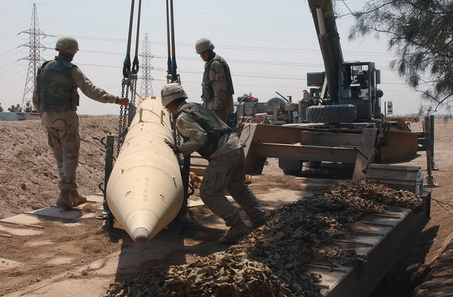 US Army (USA) Soldiers assigned to A/Company, 890th Engineer Battalion, Army National Guard (ANG) attached to the USA 3rd Infantry Division (Mechanized), use a mobile crane to remove an Iraqi Free Rocket Over Ground 7 (FROG-7) missile discovered outside of Fallujah, Iraq, during Operation IRAQI FREEDOM