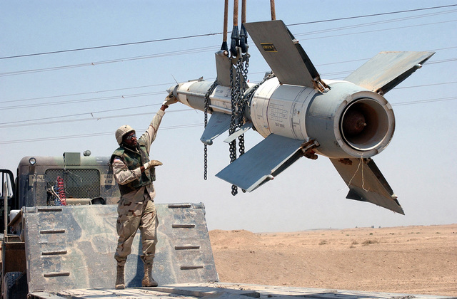 US Army (USA) Specialists (SPC) James Raine, 3rd Infantry Division, guides an Iraqi SA-3 Goa missile slated for destruction, onto a flatbed truck, after the missile was discovered outside of Fallujah, Iraq, during Operation IRAQI FREEDOM