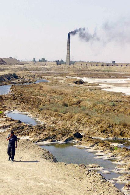 An Iraqi translator, for US Marine Corps (USMC) Marines, walks along the bank of a branch of the Euphrates River on the way back to a vehicle as he waits for the Marines to finish up their grids on a brick making plant in Ad Diwaniyah, Iraq, during Operation IRAQI FREEDOM
