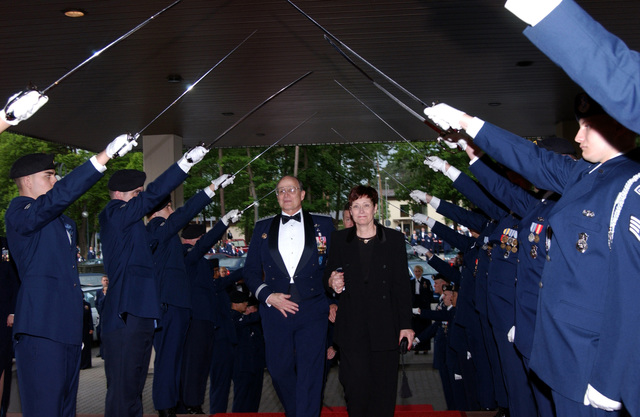 """US Air Force (USAF) General (GEN) Gregory S. Martin, Commander United States Air Forces in Europe (USAFE) and his wife Wendy Martin, , arrive at the """"Order of the Sword"""" ceremony by horse drawn carriage and stroll under the arch of swords. The """"Order of the Sword,"""" is the highest honor bestowed by the enlisted community to an Officer or other selected dignitaries"""