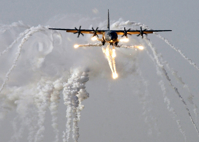 A Royal Air Force (RAF) C-130J Hercules aircraft launches countermeasures just prior to being the first coalition aircraft to land on the newly reopened military runway at Baghdad International Airport, during Operation IRAQI FREEDOM