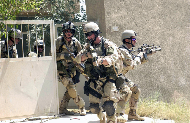 A US Air Force (USAF) Pararescue team armed with Colt 5.56mm M4A1 Carbine Rifles from Baghdad International Airport (BIAP), performs a team movement exercise through urban streets in support of Operation IRAQI FREEDOM