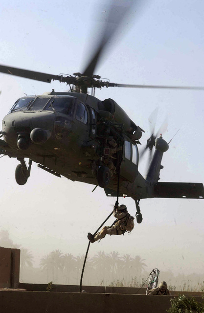 A US Air Force (USAF) Pararescue man exits an HH-60 Black hawk helicopter during a Stokes Litter practice extraction of a survivor during an Urban Operations Training Exercise (UOTE) at the Maltz training site, Baghdad International Airport (BIAP), Iraq, in support of Operation IRAQI FREEDOM