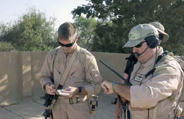 US Air Force (USAF) Major (MAJ) Paul Nevius, left, an Assistant Training Officer (ATO) assigned to the 332nd Air Expeditionary Wing (AEW) and MAJ Antonio Cunha, CHIEF of Training (CT), assigned to the 301st Rescue Squadron (RS), Patrick Air Force Base (AFB), Florida, evaluate an Urban Operations Training Exercise (UOTE) at the Maltz training site, Baghdad International Airport (BIAP), Iraq, in support of Operation IRAQI FREEDOM