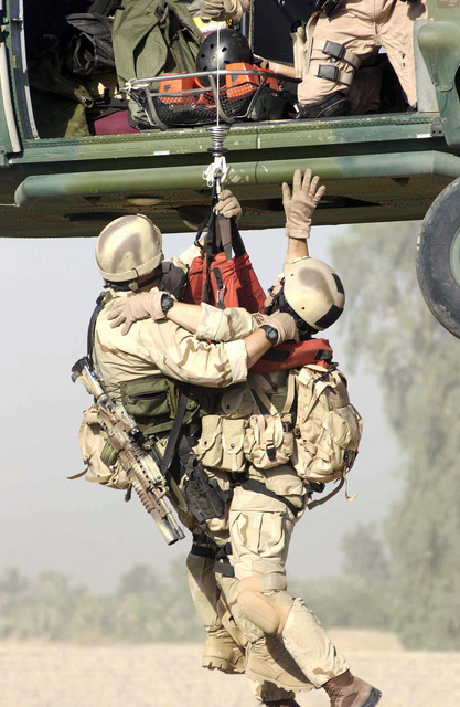 US Air Force (USAF) Pararescue personnel assigned to Baghdad International Airport (BIAP), perform a hoist extraction of a survivor during an Urban Operations Training Exercise (UOTE) at the Maltz training site, in support of Operation IRAQI FREEDOM