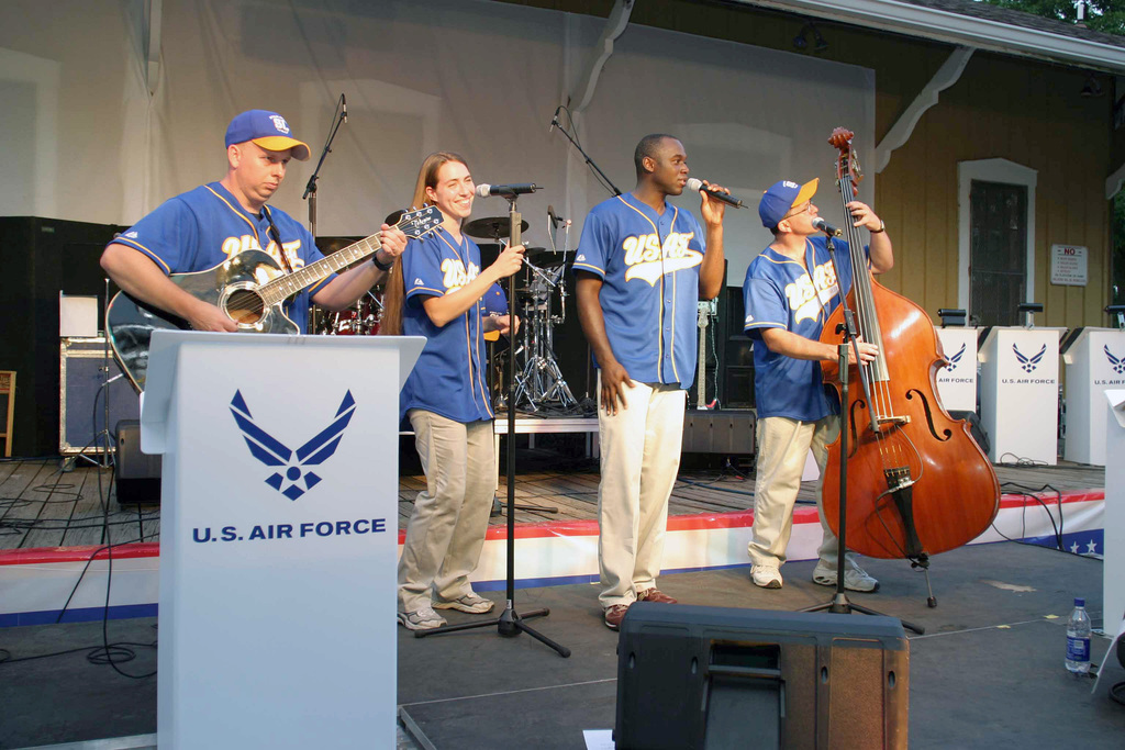 """The group known as """"Starlifter Unplugged,"""" from the United States Band of Mid-America, left to right, US Air Force (USAF) Technical Sergeant (TSGT) Terry Cottrell, guitarist, SENIOR AIRMAN (SRA) Victoria Cronsell, vocalist, AIRMAN First Class (A1C) Brian Owens, vocalist and TSGT Guy Canton, bass, perform a bluegrass tune for spectators at Mascouta's Fourth of July Celebration"""