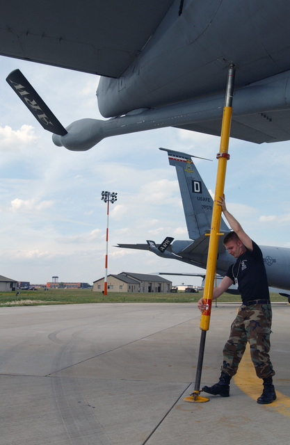 US Air Force (USAF) STAFF Sergeant (SSGT) Robert Scariano, with the 100th Aircraft Maintenance Squadron (AMXS), Royal Air Force (RAF) Mildenhall, England (ENG), places a cargo loading strut under a KC-135R Stratotanker, prior to its fuel cargo being loaded aboard