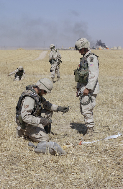US Air Force (USAF) STAFF Sergeant (SSGT) Ryan Groves, left, with the 506th Expeditionary Civil Engineer Squadron (ECES), Explosive Ordnance Disposal (EOD) team and US Army (USA) Sergeant (SGT) Salvdor Broes III, with the 173rd Combat Support Company (CSC), a Combat Engineer, dispose of an unexploded device found by local villagers, outside Kirkuk, Iraq, during Operation IRAQI FREEDOM
