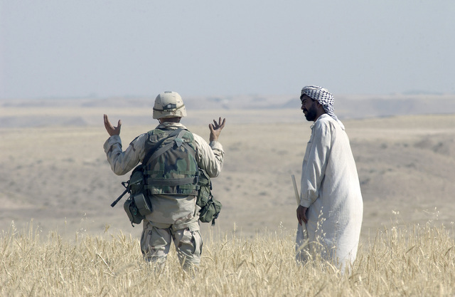 US Army (USA) STAFF Sergeant (SSGT) Corey Deibel, with the 173rd Combat Support Company (CSC), a Combat Engineer, explains to a local villager, outside Kirkuk, Iraq, the dangers of an unexploded device during Operation IRAQI FREEDOM