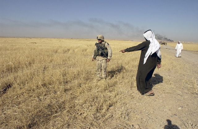 US Army (USA) STAFF Sergeant (SSGT) Corey Deibel, with the 173rd Combat Support Company (CSC), a Combat Engineer, is shown the exact location of an unexploded device by a local villager, outside Kirkuk, Iraq, during Operation IRAQI FREEDOM