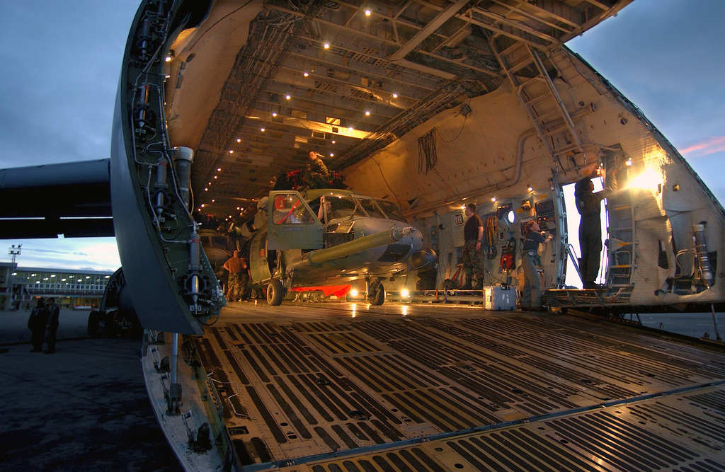 US Air Force (USAF) Loadmasters from the 301st Airlift Squadron (AS), Travis Air Force Base (AFB), California, along with members of the 85th Maintenance Squadron (MXS) and 56th Rescue Squadron (RS), Naval Air Station (NAS) Keflavik, Iceland, prepare to unload HH-60G Pave Hawk helicopters from a C-5 Galaxy cargo aircraft at Lungi, Sierra Leone, during a Humanitarian Assistance mission
