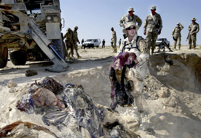 US Army (USA) CHIEF Warrant Officer (CWO) John Massie, collects clothing and other belongings found at a mass gravesite near Mosul, Iraq, during Operation IRAQI FREEDOM. CWO Massie is assigned to the USA Criminal Investigation Command (CID) as a Special Agents and Department of Defense Forensic Pathologists, investigating a mass grave crime scene to gather evidence for possible war crime trials
