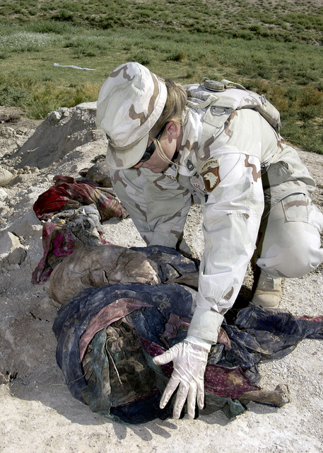 US Army (USA) Sergeant First Class (SFC) Dawn Byrnes collects clothing and other belongings found at a mass gravesite near Mosul, Iraq, during Operation IRAQI FREEDOM. SFC Byrnes is assigned to the USA Criminal Investigation Command (CID) as a Special Agents and Department of Defense Forensic Pathologists, investigating a mass grave crime scene to gather evidence for possible war crime trials