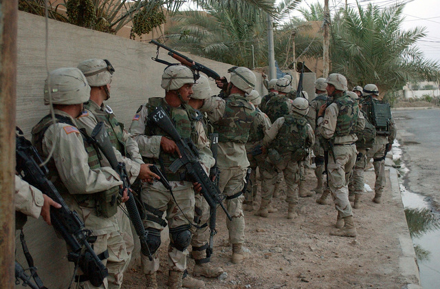 US Army (USA) Soldiers assigned to the 115th Military Police (MP) Company, Army National Guard (ANG) prepare to enter an Iraqi house believed to be the site of a weapons cache in Fallujah, Iraq, during Operation IRAQI FREEDOM
