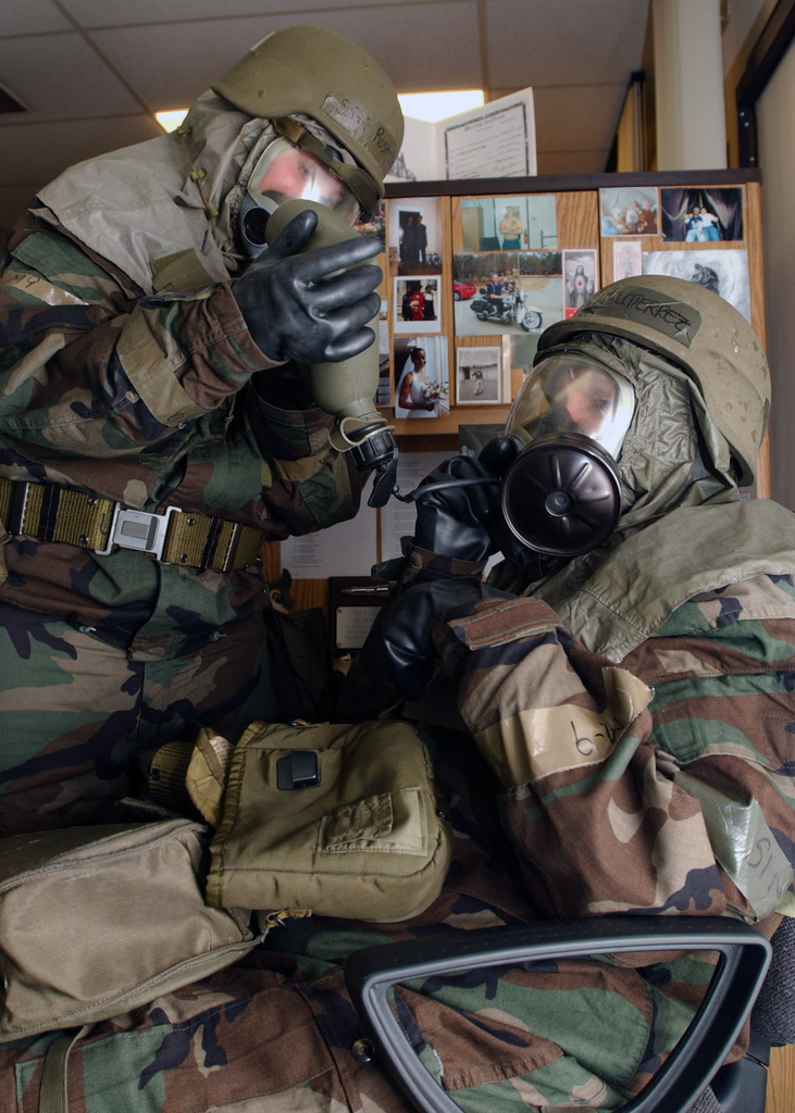 US Air Force (USAF) STAFF Sergeant (SSGT) Staci Rosenberger, assists Technical Sergeant (TSGT) Christine Gutierrez, in drinking water through her MCU-2A/P mask while dressed in Mission-Oriented Protective Postures level 4 (MOPP 4) gear, during a Local Salty Nation exercise