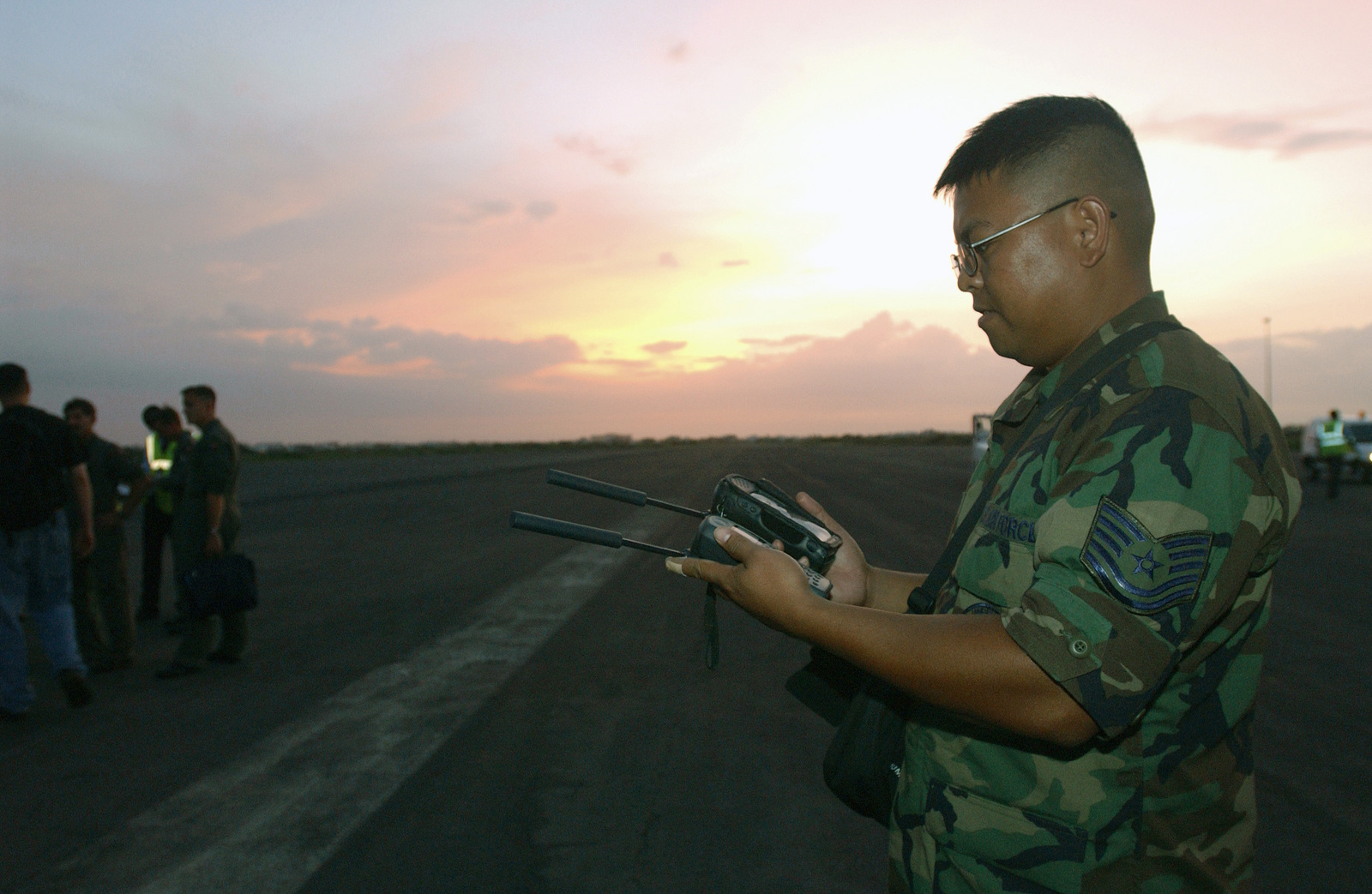 US Air Force (USAF) Technical Sergeant (TSGT) Rodel Delacruz, deployed from the 52nd Communications Squadron (CS), Spangdahlem Air Base (AB), Germany (DEU), verifies that both satellite telephones initialize upon arrival at the Dakar International Airport in Senegal, Africa