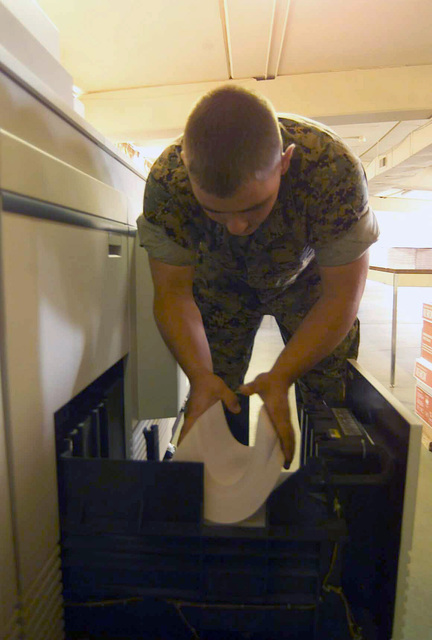 US Marine Corps (USMC) Corporal (CPL) Timothy Young, 1ST Marine Division Combat Camera and Printing, inserts copy paper into a copier at the 1ST Marine Divisions, Combat Camera and Printing shop at Camp Margarita, Camp Pendleton, California (CA)