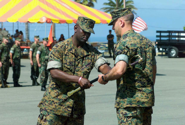 US Marine Corps (USMC) Sergeant Major (SGM) Alvin Griffin (left), 1ST Light Armored Reconnaissance Battalion (1ST LAR), Marine Corps Base (MCB) Camp Pendleton, California (CA), gives the Non-commissioned Officer (NCO) sword to USMC Lieutenant Colonel (LTC) W.R. Constantini, Commanding Officer, 1ST LAR, during the Sergeant Major Relief and Appointment Ceremony on the 1ST LAR parade deck, as he relinquishes his command