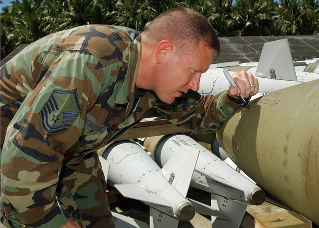 US Air Force (USAF) MASTER Sergeant (MSGT) Brett Workman, Network SPECIALIST writes a message on a MK-82 500-pound general purpose bomb while deployed at an undisclosed location during Operation ENDURING FREEDOM