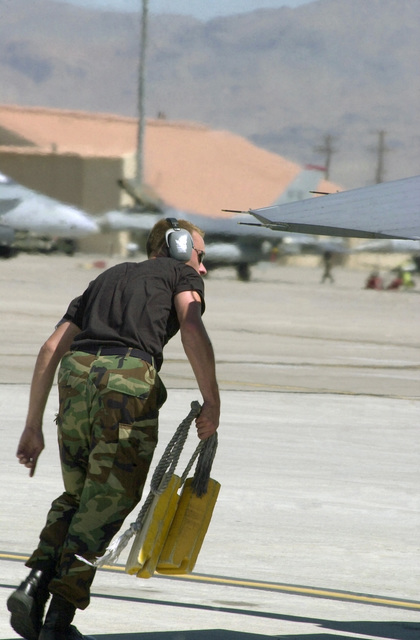 US Air Force (USAF) STAFF Sergeant (SSGT) Aaron M. Hudson, a dedicated Crew CHIEF working with both the 510th and 555th Fighter Squadrons, removes the wheel chocks from an aircraft, while participating in the AIR WARRIOR and RED FLAG Training Exercises, held at Nellis Air Force Base (AFB, Nevada (NV)