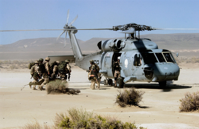 US Navy (USN) SEAL Team Members carry a survivor on a stretcher to be loaded aboard a HH-60F Seahawk helicopter during the rescue training exercise DESERT RESCUE XI. The exercise is the premiere Search And Rescue (SAR) training exercise involving all branches of the US Military and is conducted at the ranges of Fallon Naval Air Station, Nevada (NV)